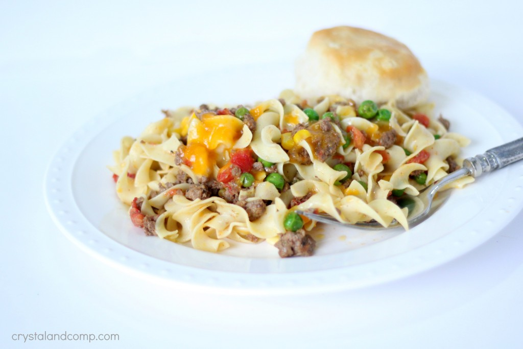 wide egg noodles and hamburger meat with peas corn and cheese