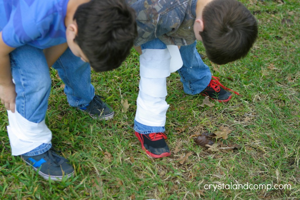 kids doing mummy relay halloween game