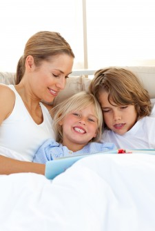 Pretty Mother And Her Children Reading Book Lying In Bed