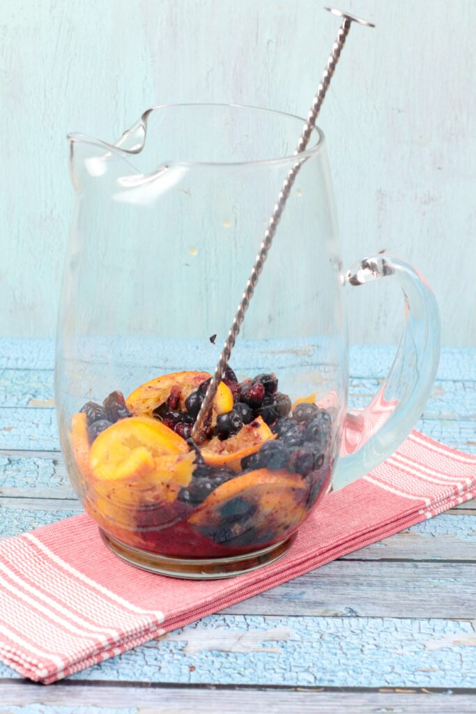 Glass pitcher with orange and blueberries with a large spoon on a pink napkin. Step 2 of orange blueberry water recipe.