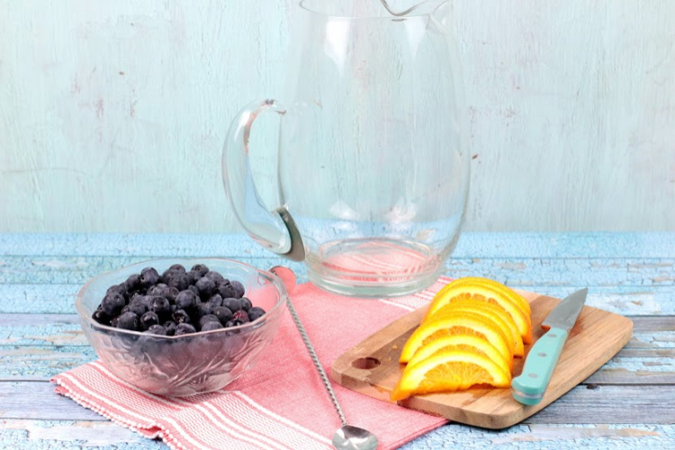 Ingredients for orange blueberry infused water. Blueberries, sliced oranges, long handled spoon and a clear glass pitcher.